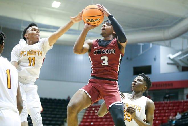 Putnam City North's Kole Johnson blocks Owasso's Trenton Ellison's attempted shot during a Class 6A boys basketball quarterfinal Thursday at Skiatook High School.