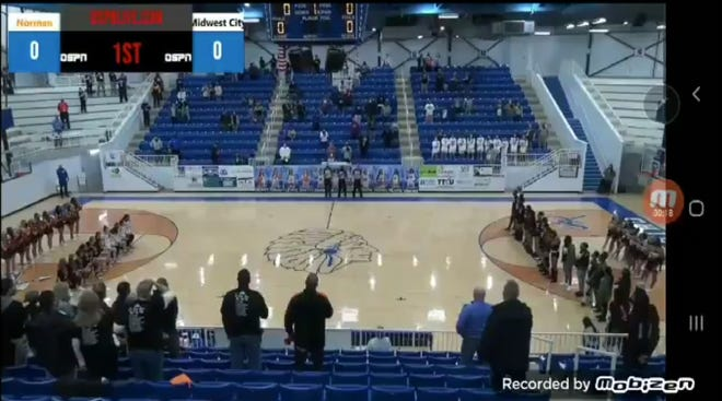 A screengrab from an NFHS Network broadcast on Thursday shows members of the Norman girls basketball team kneeling during the National Anthem. A hot microphone caught announcers for the broadcast calling the Norman girls
