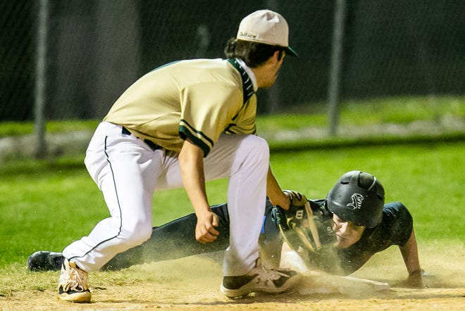 Trinity Catholic's Cole Stephens looks to tag out Belleview's Wes Arrants as Arrants dives onto base safe.