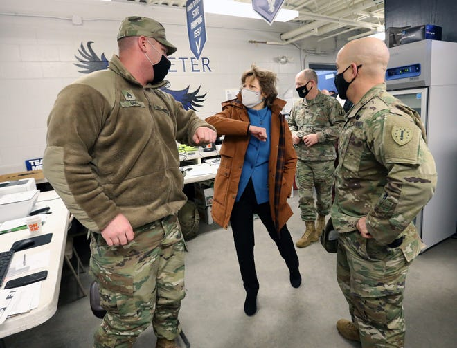 National Guard Staff Sgt. Day and U.S. Senator Jeanne Shaheen tap elbows as they meet in the command center during her tour at the mass vaccination site at Exeter High School Friday.