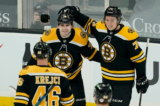 Boston Bruins left wing Jake DeBrusk (74) celebrates his goal with Charlie McAvoy (73) and David Krejci (46) during the second period of the team's NHL hockey game against the New York Rangers, Thursday, March 11, 2021, in Boston. (AP Photo/Elise Amendola)
