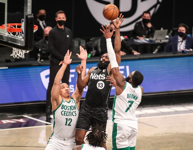 Mar 11, 2021; Brooklyn, New York, USA; Brooklyn Nets guard James Harden (13) shoots over Boston Celtics forward Grant Williams (12) and guard Jaylen Brown (7) in the fourth quarter at Barclays Center. Mandatory Credit: Wendell Cruz-USA TODAY Sports