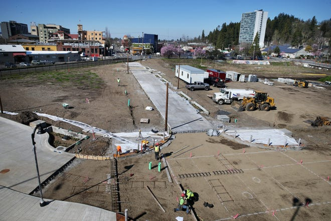 Crews work on additions to the roadway along East Fifth Avenue as it enters the new Downtown Riverfront Park area from the downtown Eugene Market District, as seen from the Ferry Street Viaduct.