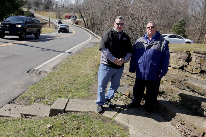 Edward Robinson, (left) director of programs for Carrollton Schools, and Mark Wells, Carrollton village administrator, stand at the end of sidewalk along state Route 332 near the schools. Officials want to build a sidewalk to reduce risk to students who are walking to school along a busy highway.