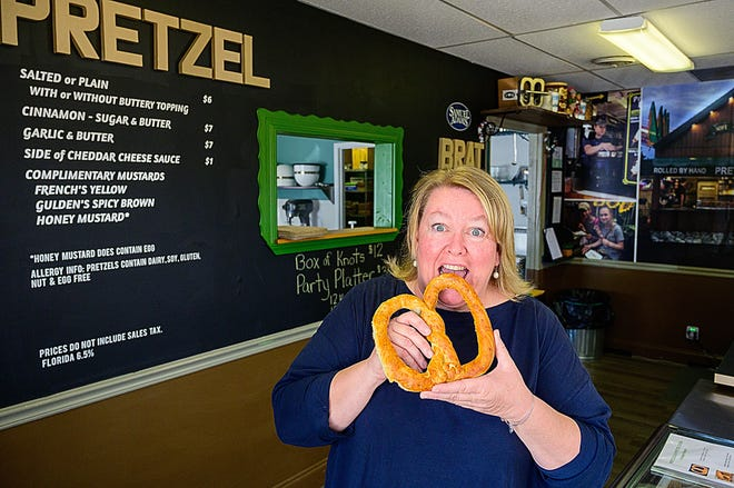 Samantha Fairlie, the Pretzel Lady, prepares to take a bite of one of her hand-rolled pretzels in her store in St. Augustine last week.