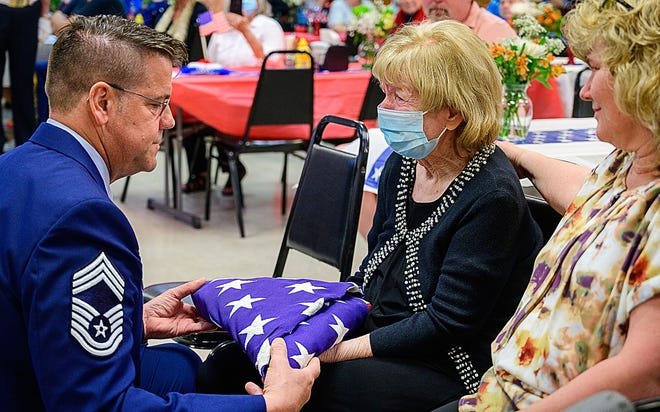 Retired U.S. Airforce Chief Master Sgt. Galen Wilson comforts his mother-in-law, Sylvia Klett, after presenting her a flag at a memorial service for her husband, Ray Klett, at the Veterans of Foreign Wars Bryan Tutten Memorial Post 2391 in St. Augustine on Friday. Klett, who was 98 when he died Feb. 27, was the last member of the VFW post to serve in World War II.