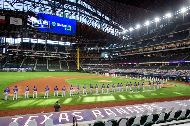 The Texas Rangers and Colorado Rockies line the foul lines of Globe Life Field before an opening day baseball game in Arlington in this July 24, 2020, file photo. The Texas Rangers could have a full house for their home opener next month after debuting their new 40,518-seat stadium without fans in the stands for their games last season.