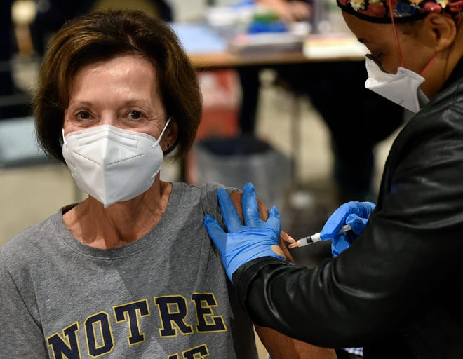 Billie Bankoff, 71, of Lakewood Ranch, a big fan of Notre Dame, receives a vaccination from Weedor Toe LPN from the Florida Department of Health, who was assisting during the Sarasota Memorial Hospital vaccination event on Saturday, Jan. 9, 2021. THOMAS BENDER/HERALD-TRIBUNE