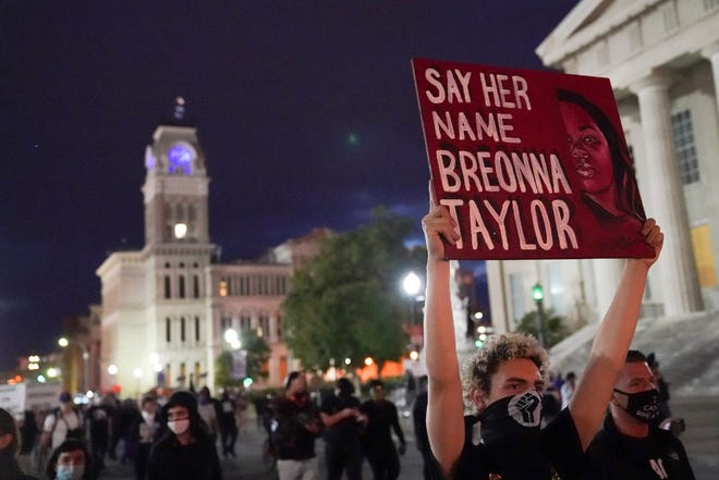 In this Sept. 24 photo, protesters march in Louisville, Kentucky. The three Louisville police officers who fired their guns in the fatal raid at Breonna Taylor's apartment avoided homicide charges. But an ongoing federal probe could expand beyond the officers who conducted the raid. The warrant that sent the police to Taylor's home a year ago and how it was obtained are under review by federal investigators. And there are signs the investigation could range into the Louisville police response to protests after the shooting.