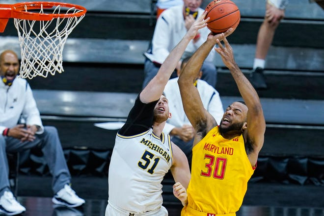 Maryland forward Galin Smith (30) is fouled as he shoots over Michigan forward Austin Davis (51) in the first half of an NCAA college basketball game at the Big Ten Conference tournament in Indianapolis, Friday, March 12, 2021. (AP Photo/Michael Conroy)
