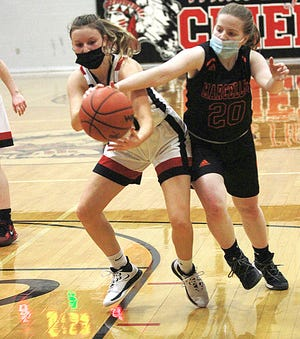 White Pigeon's Ashley Delayre and Marcellus' Hannah Wildes battle for a loose ball in prep hoops action on Thursday.