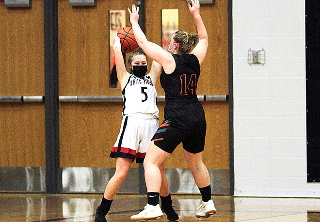 White Pigeon's Taylor Wesolek looks for a teammate while being defended in the corner by Abby Voss of Marcellus on Thursday.