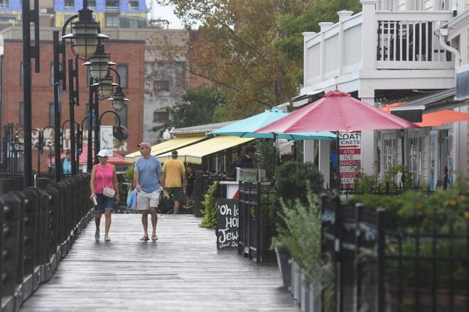 People walk along the Riverwalk in downtown Wilmington, N.C. The Wilmington City Council is considering refinancing a bond to fund improvements to the Riverwalk, streets and other capital projects.