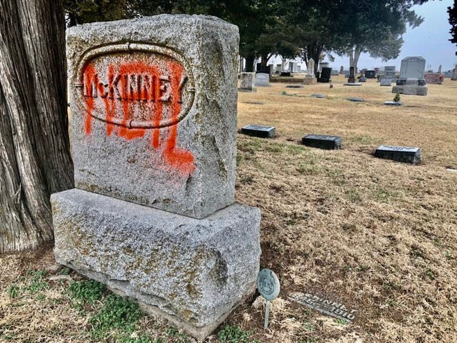 "This gravestone at southeast Topeka's Pleasant Hill Cemetery was desecrated this week by someone who spraypainted the word ""Neil"" on it."