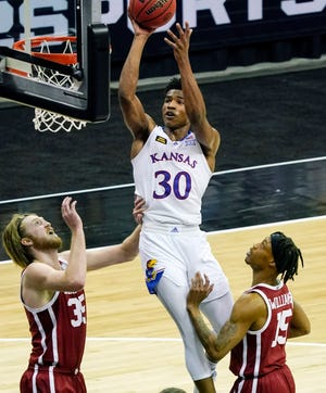 Kansas guard Ochai Agbaji puts up a shot attempt as Oklahoma's Brady Manek, left, and Alondes Williams look on during the second half of Thursday's game at T-Mobile Center in Kansas City, Mo. Agbaji scored a career-high 26 points in the No. 11-ranked Jayhawks' 69-62 victory over the No. 25 Sooners.
