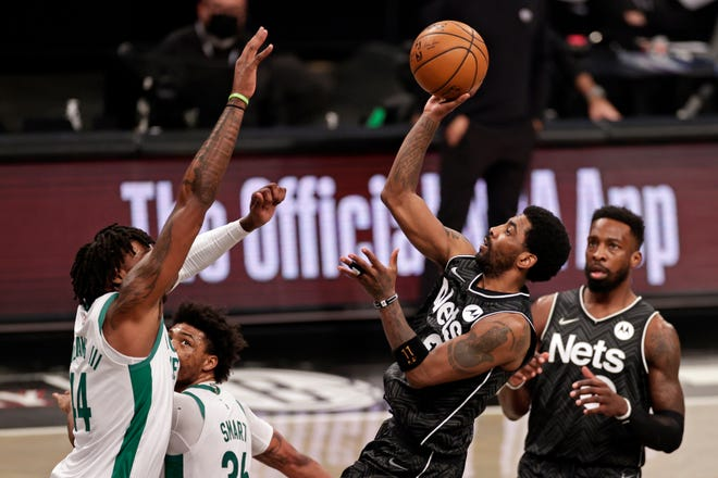 Brooklyn guard Kyrie Irving shoots over Boston center Robert Williams III during the first half of Thursday's game.