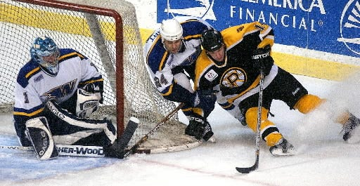 The IceCats' Mike Stuart (24) derails Providence's Carl Corazzini, right, on a wraparound attempt, with Curtis Sanford tending goal during a game in 2003.