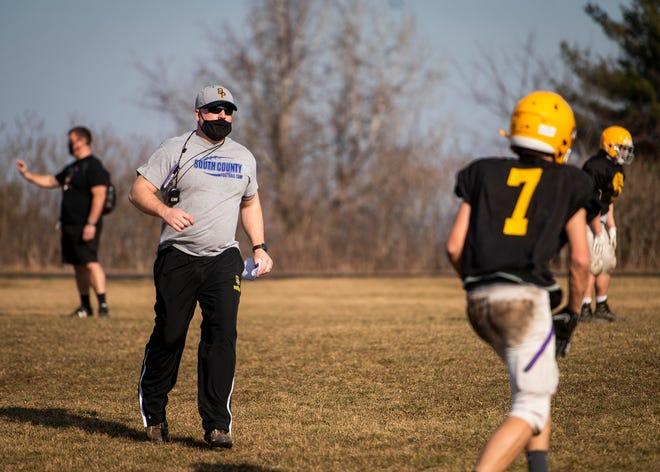 Bay Path football coach Cody Giampa runs his Minutemen through a practice last month.