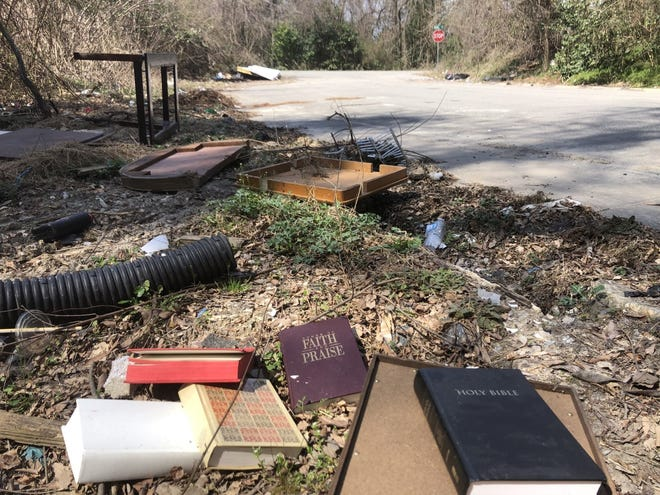 Discarded bibles and trash litter the roadside near woods where a man's body was found by a Fayetteville city worker early Friday.