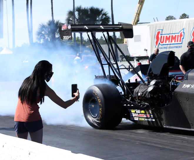 A race team associate takes a photo as an alcohol dragster does a burnout on the track before a race Friday at the AMALIE Motor Oil NHRA Gatornationals at Gainesville Raceway.