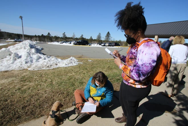 Saggy Travis and Kendra Payne fill out paperwork outside of a pop-up vaccination site at the Monticello Raceway Friday. Their 8-week old dog Taj is watching.