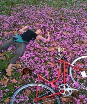 Tesa Burch takes a moment to smell the flowers during a bike ride.