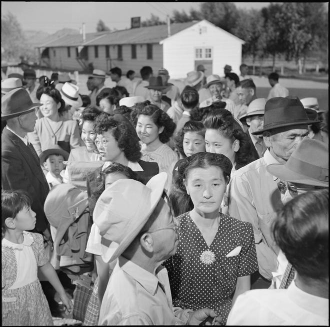 Japanese Americans interned at the relocation camp in Poston, Arizona stand in line before the departure station where they received their ration books and bus tickets after being released in September 1945.