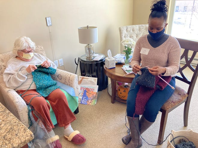 Cornerstone at Canton Lead Resident Care Associate Sophia Nyokabi knits scarves with resident Ethel Conaxis.