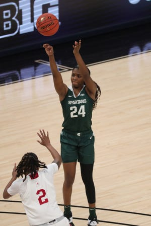 Michigan State guard Nia Clouden (24)  scores against Indiana guard Keyanna Warthen (2) during the Big Ten tournament on Thursday, March 11, 2021, at Bankers Life Fieldhouse in Indianapolis.