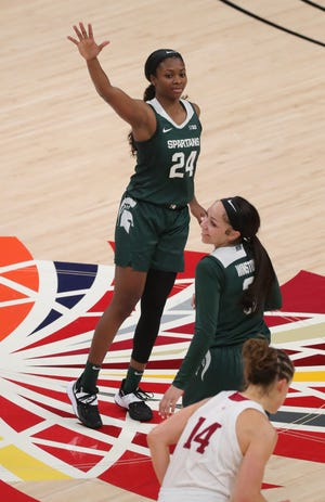 Michigan State Spartans guards Nia Clouden (24) and  Alyza Winston (3) celebrate after Clouden's 3-pointer against Indiana Hoosiers forward Mackenzie Holmes (54) during the Big Ten tournament on Thursday, March 11, 2021, at Bankers Life Fieldhouse in Indianapolis.
