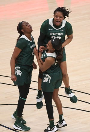 Michigan State Spartans Mardrekia Cook (2) Janai Crooms (23) and Nia Clouden (24) celebrate the 69-61 quarterfinal win over the Indiana Hoosiers during the Big Ten tournament on Thursday, March 11, 2021, at Bankers Life Fieldhouse in Indianapolis.