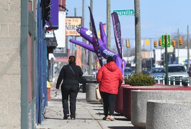 Orang-orang berjalan di sepanjang Jalan Warren Timur dekat Jalan Courville pada hari Jumat, 12 Maret 2021. Rencana Kerangka Kerja Lingkungan Warren Timur Cadieux berharap dapat memperbaiki lingkungan tersebut. Max Ortiz, Berita Detroit