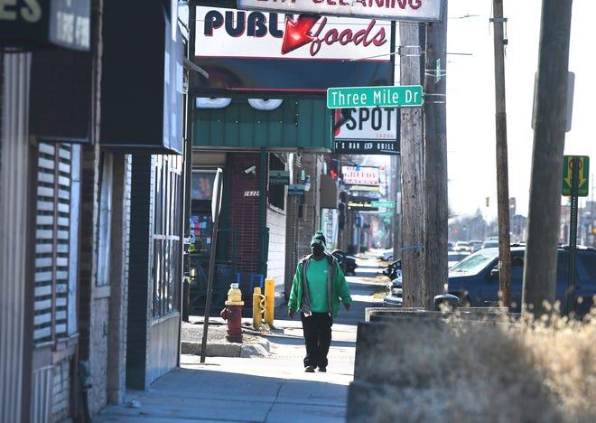 Seseorang berjalan di sepanjang East Warren Avenue dekat Three Mile Drive pada hari Jumat, 12 Maret 2021. Rencana Kerangka Lingkungan East Warren Cadieux berharap dapat memperbaiki lingkungan tersebut.