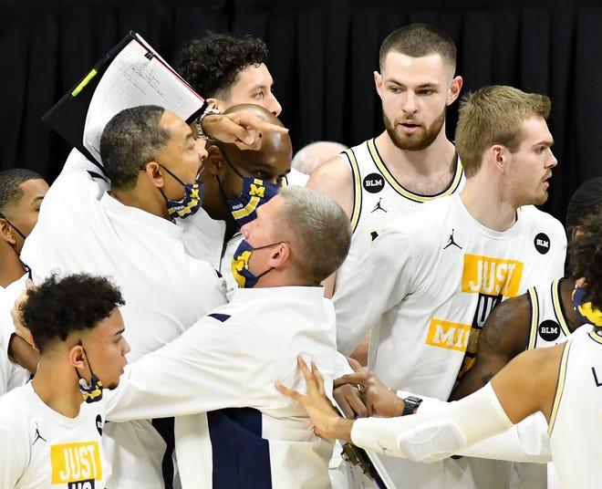 Pelatih dan pemain Michigan mencoba menenangkan pelatih kepala Juwan Howard selama konfrontasi di babak kedua.