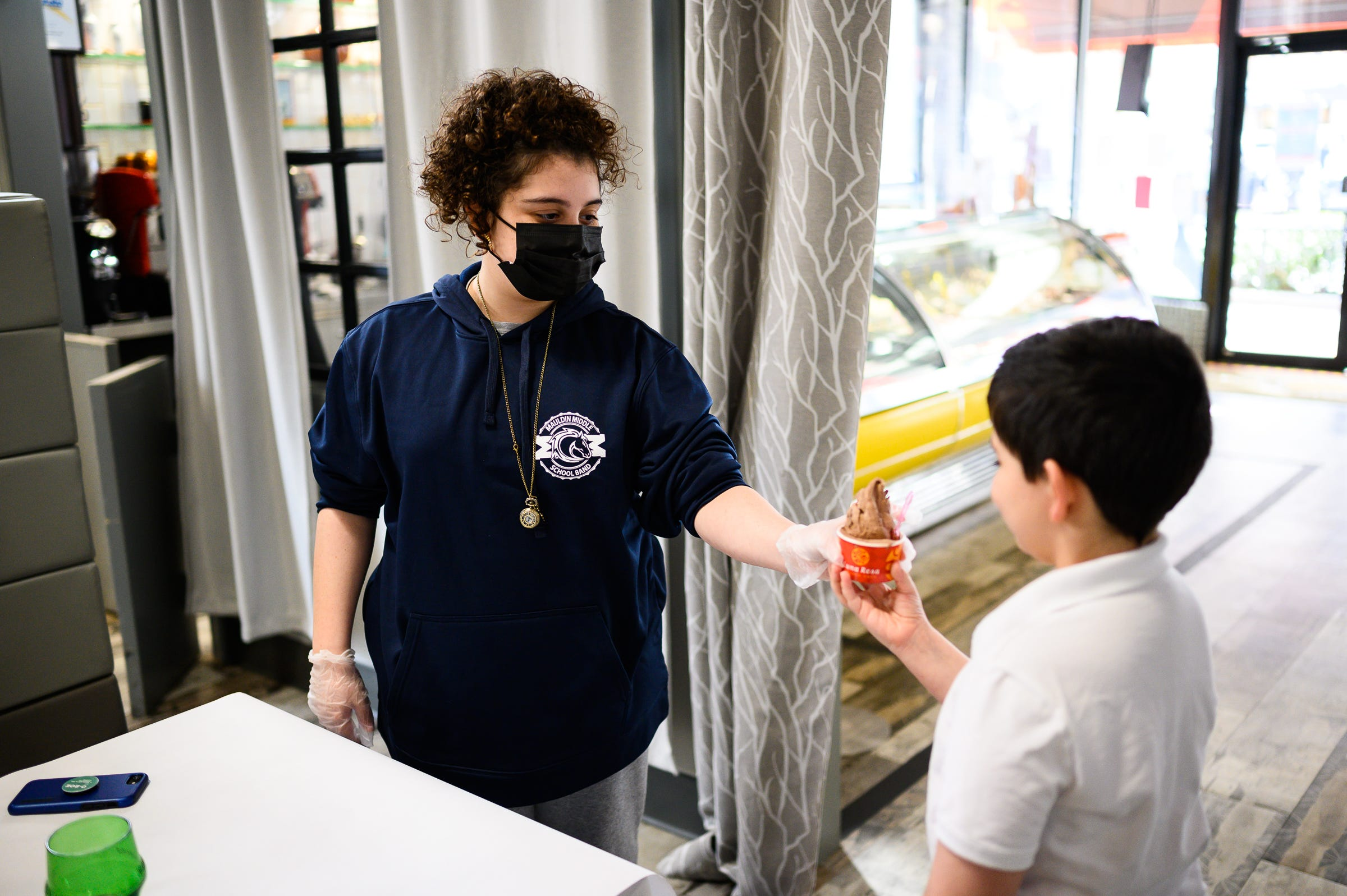 Mia Ortiz hands her brother Luca a gelato at Luna Rosa Gelato Cafe downtown Thursday, March 11, 2021.