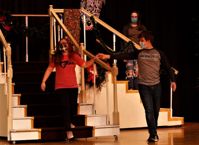 """Malina Hunt, left, is escorted by Will Loudon down the stairs during a Lancaster High School Drama Club rehearsal of """"Annie"""" on Wednesday, March 10. The students in the club are excited to perform to in-house audiences and on demand, especially after last year's performance was canceled because of the coronavirus pandemic."""