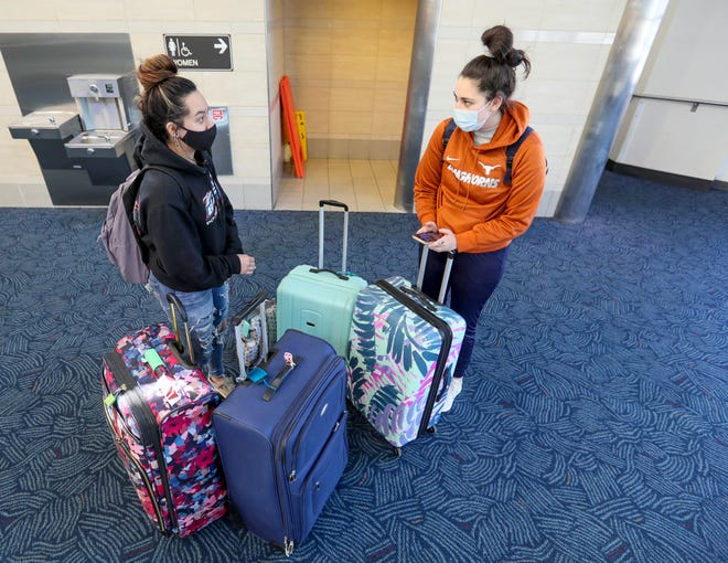 Dakota Mendez, 20, left, and Greta Hetrick, 20, socialize while they wait for the rest of their party to return at Milwaukee Mitchell International Airport on Friday, March 12, 2021. Mendez and Hetrick are on spring break heading to Puerto Rico.