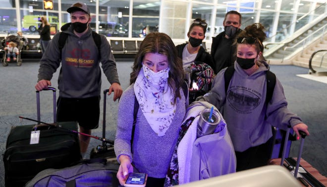 Alex, left, Sandra, middle, Abby, middle back, Chris and Maggie Hanmann, right, check in for their flight at Milwaukee Mitchell International Airport on Friday, March 12, 2021. Alex, Abby and Maggie are on spring break heading to Ft. Lauderdale, Fla.