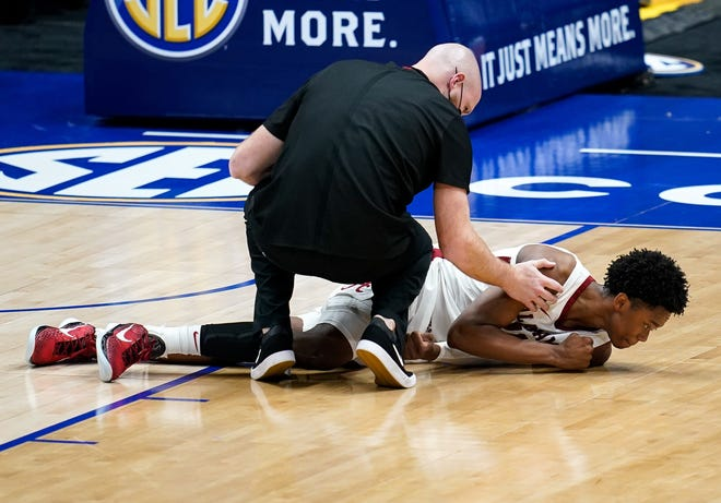 Alabama guard Joshua Primo (11) is examined after an injury during the second half of the SEC Men's Basketball Tournament game against Mississippi State at Bridgestone Arena in Nashville, Tenn., Friday, March 12, 2021.