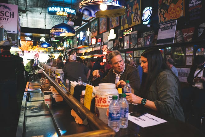 Gov. Bill Lee is pictured sitting inside Robert's Western World with Emily Ann Jones.