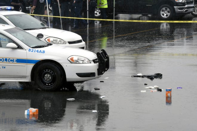 Debris is seen in the parking lot of a Dollar General store on Brick Church Pike as police investigate the scene where an MNPD officer and 31-year-old woman were shot on Friday, Mar. 12, 2021.
