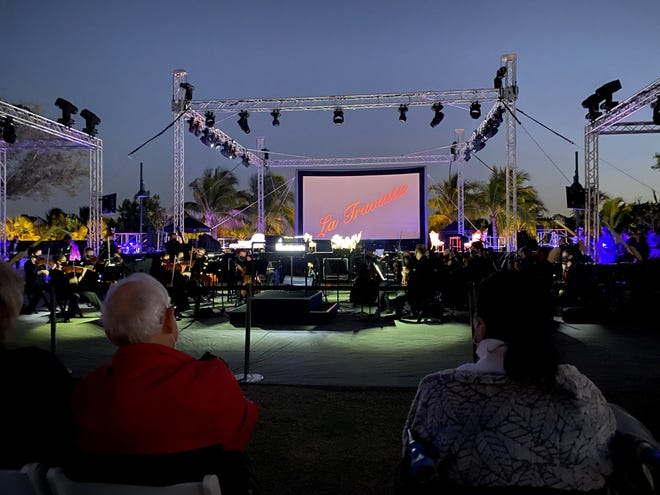 """The audience and orchestra ready Thursday for """"La Traviata,"""" the first opera at Baker Park, which plays on the stage in front of the screen."""