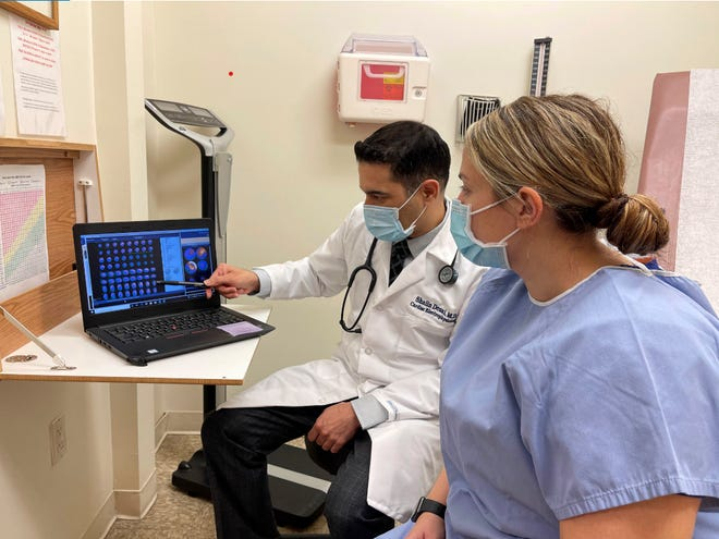 Holy Name Medical Center cardiac electrophysiologist Shalin Desai, MD, discusses a patient's EKG with her.