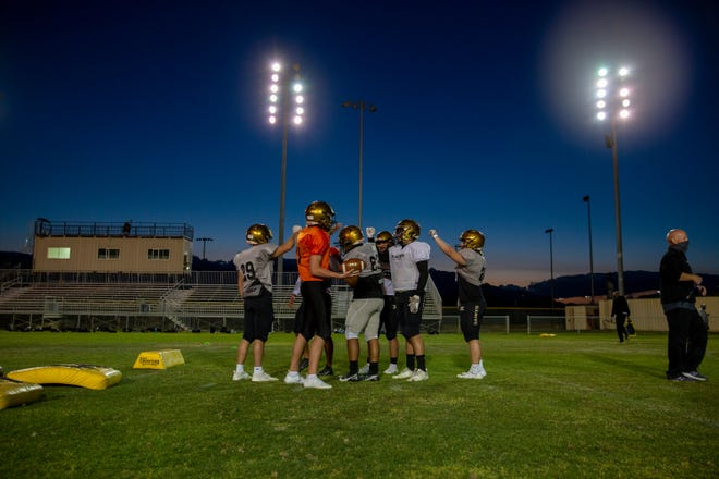 Xavier Prep football players rally before a water break during practice in Palm Desert, Calif., on March 9, 2021.