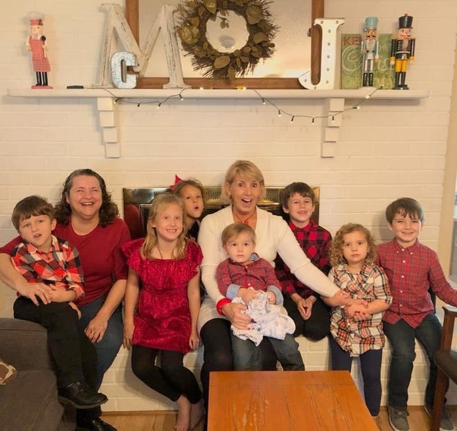 Cylea Lyrio, center, and her sister pose for a holiday photo with Lyrio's seven grandchildren.