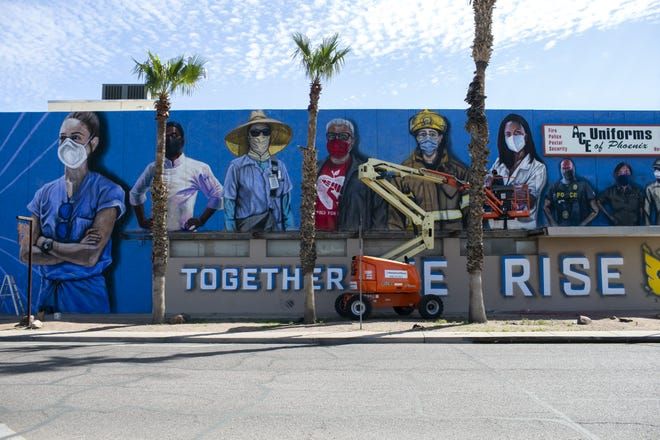 Artist Darrin Armijo-Wardle helps finish a mural by Hugo Medina honoring first responders in Phoenix on Mar. 11, 2021. Medina was injured from a fall while working on the mural and called in Armijo-Wardle and others to help finish it.