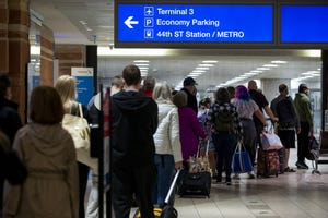 Travelers wait to pass through security at Terminal 4 in Sky Harbor International Airport in Phoenix, Ariz., on March 11, 2021.