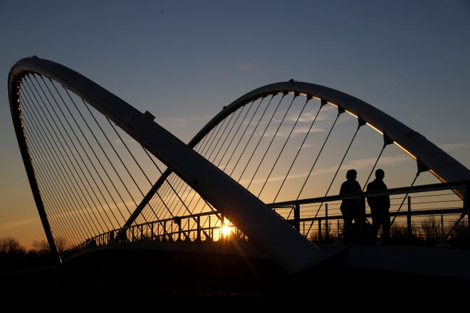 People cross Peter Courtney Minto Island Bridge as the sun sets. The bridge connecting Minto Brown and Riverfront parks offers ways to link trails for longer hikes.