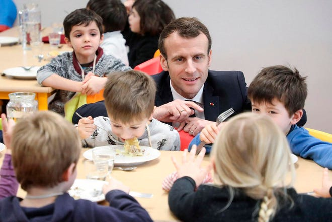 In this Jan.18, 2019, photo, French President Emmanuel Macron meets pupils as he visits a school canteen in Saint-Sozy, southwestern France. By taking meat off the menu at school canteens, the Green Party mayor of Lyon has kicked up a storm of protest and debate in a country increasingly asking questions about the environmental costs of its meaty dietary habits.