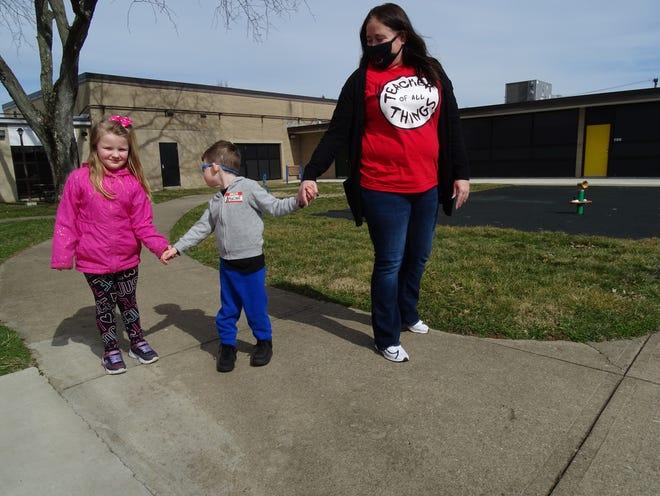 Starlight preschool teacher Katie Murphy, Madellen Goldsmith and Brayden Kennedy enjoy the sun at recess on Friday, March 12, 2021.